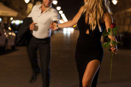Photo pour An elegant couple holding hands when running on a date at night - image libre de droit