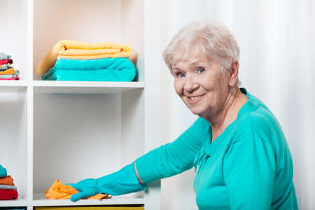 Foto de Smiling senior woman cleaning house before Christmas - Imagen libre de derechos