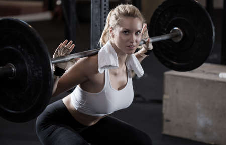Foto de Image of girl making squat with barbell - Imagen libre de derechos