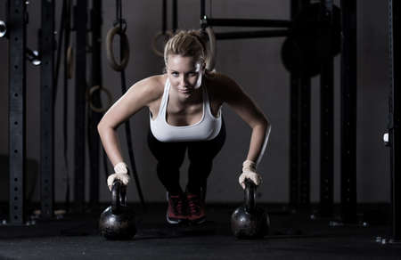 Photo for Young strong girl doing push-ups na kettlebells - Royalty Free Image