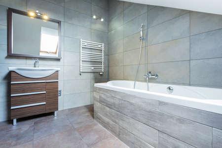Photo pour Bathroom interior with bath and wooden shelf - image libre de droit