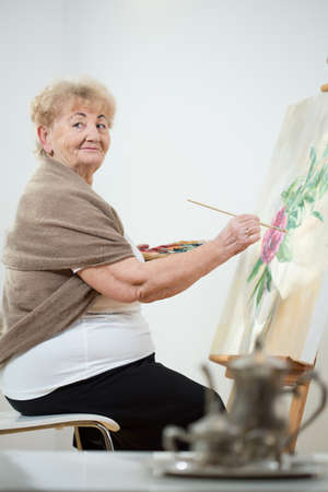 Photo for Elderly artistic woman painting a picture - Royalty Free Image