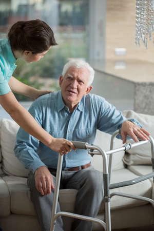 Foto de Disabled man using walking frame and helpful nurse - Imagen libre de derechos