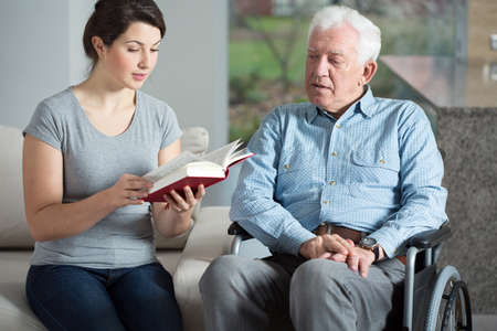 Photo for Senior care assistant reading book elderly man - Royalty Free Image