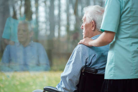 Foto de Nurse assisting disabled senior man using wheelchair - Imagen libre de derechos