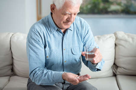Photo pour Ill senior man taking pill and drinking water - image libre de droit