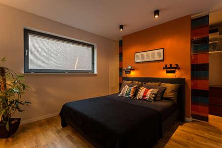 Photo pour Designer bedroom with orange wall and color cushions - image libre de droit