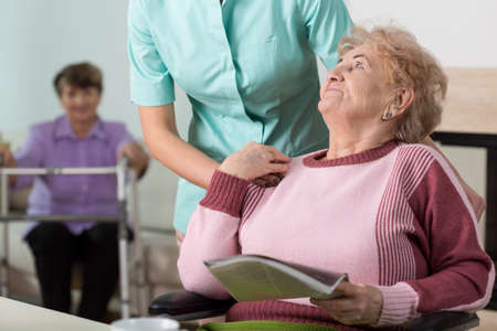 Photo pour Young caring therpist and senior woman in nursing home - image libre de droit