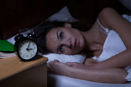 Photo pour Woman with insomnia lying in bed with open eyes - image libre de droit