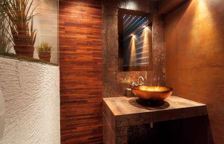 Foto de Interior of expensive bathroom with golden sink - Imagen libre de derechos