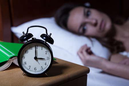 Foto de Alarm clock on night table showing 3 a.m. - Imagen libre de derechos