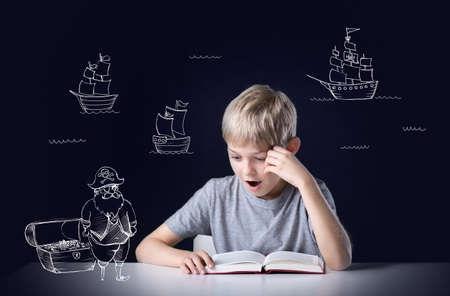 Photo pour Little boy's imagination during reading the adventure book - image libre de droit