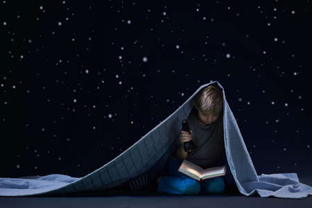 Foto de Little boy reading book at night under the blanket - Imagen libre de derechos