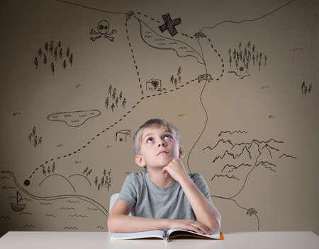 Photo pour Little kid thinking about treasure map from his adventure book - image libre de droit