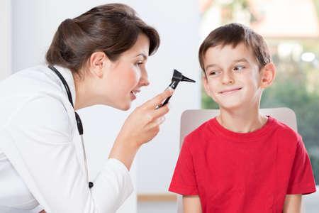 Foto de Young pretty doctor examinating little boy\'s hearing - Imagen libre de derechos