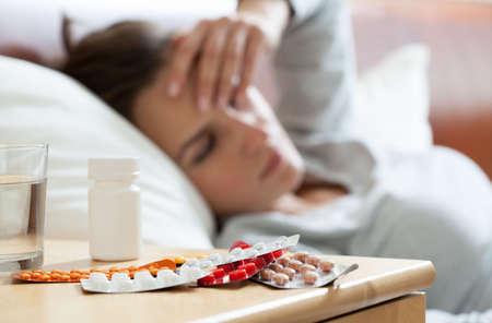 Foto de A lot of medicines on night table in bedroom - Imagen libre de derechos