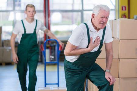 Foto de Senior employee having heart attack in workplace - Imagen libre de derechos