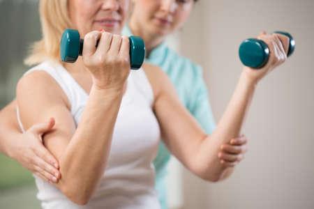 Foto de Woman exercising with dumbbells in rehabilitation clinic - Imagen libre de derechos