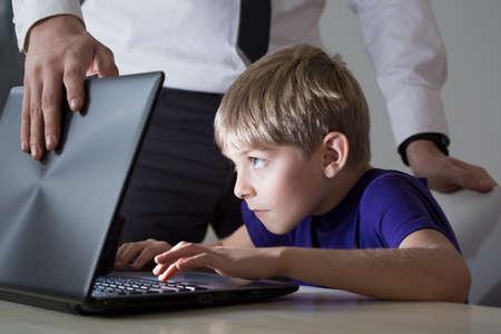 Photo pour Dad don't allow son using his laptop - image libre de droit
