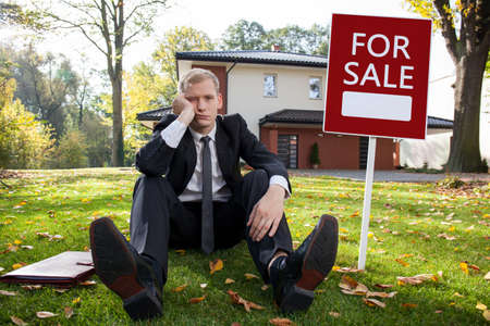 Photo pour Worried real estate agent and house for sale - image libre de droit