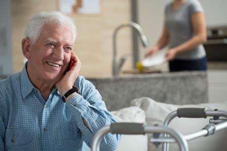 Foto de Elderly sick man talking the mobile phone - Imagen libre de derechos