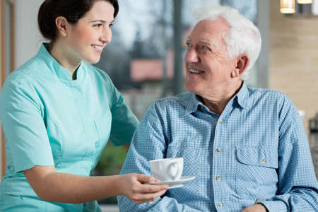 Photo for Young pretty nurse serving the cup of coffee to elderly smiling man - Royalty Free Image