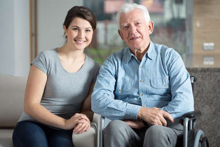 Photo for Young pretty female caretaker and elderly man on a wheelchair - Royalty Free Image