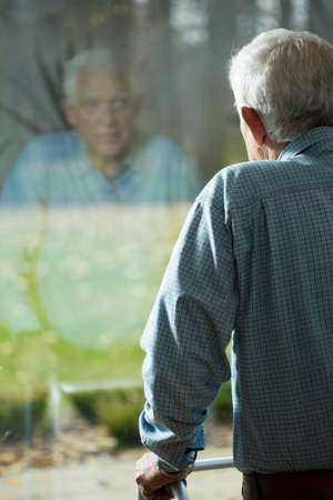 Photo for Elderly weak man looking through the hospital window - Royalty Free Image