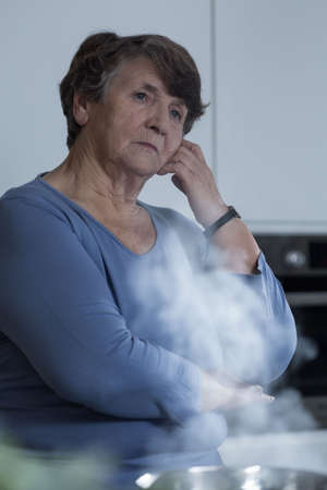 Senior sorrowful woman deep in thought in the kitchen