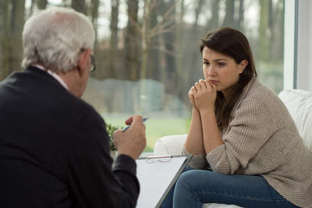 Foto de Sad teenage girl talking with her psychologist - Imagen libre de derechos