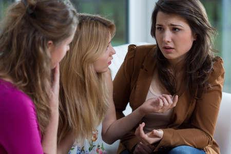 Foto de Three pretty friends having a serious conversation - Imagen libre de derechos
