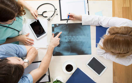 Photo for Doctors sitting around the table and interpreting x-ray image - Royalty Free Image