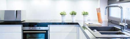 Photo pour View of black and white kitchen interior - image libre de droit