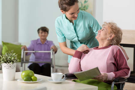 Foto de Helpful nurse working in old people's home - Imagen libre de derechos