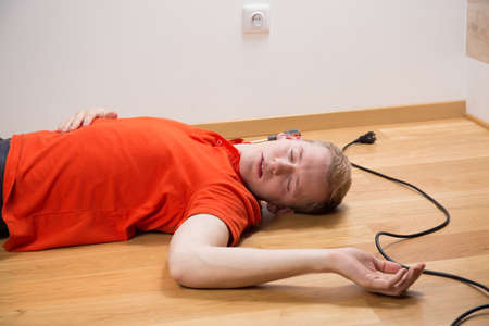 Photo pour Electrocuted unconscious electrician lying on the floor - image libre de droit