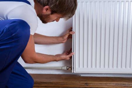 Photo pour Handyman fix the radiator in the room - image libre de droit