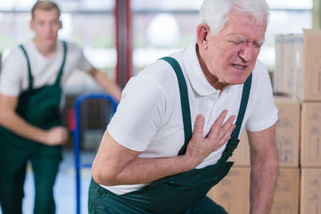 Foto de Close-up of older warehouse worker having a heart attack - Imagen libre de derechos