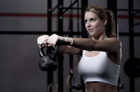 Photo for Young beautiful woman exercising with kettlebell - Royalty Free Image
