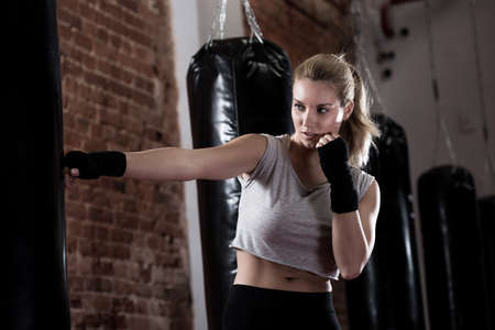Horizontal view of girl training kick boxing