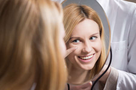 Foto de Woman putting in contact lens at optician's office - Imagen libre de derechos