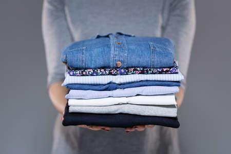Foto de Woman holding folded clothes in hands - Imagen libre de derechos