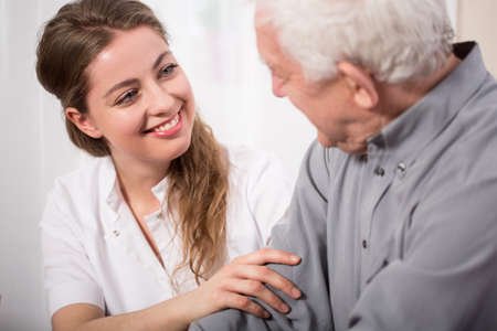 Photo for Picture of smiling nurse assisting senior man - Royalty Free Image
