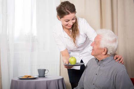 Foto de Helpful nurse and smiling pensioner at home - Imagen libre de derechos