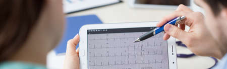 Foto de Modern cardiologists analyzing patient's electrocardiogram on tablet - Imagen libre de derechos