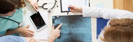 Photo pour Image of young doctors analyzing pelvis x-ray - image libre de droit