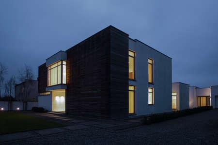Photo pour Illuminated windows in detached house - picture at night - image libre de droit