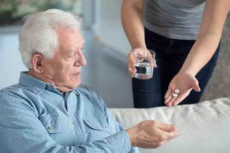 Foto de Close-up of ill senior man taking medicine - Imagen libre de derechos