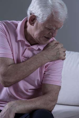 Photo pour Senior sad man with acute pain in his shoulder joint - image libre de droit