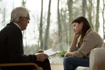 Foto de Young attractive sad woman sitting at psychologist's office - Imagen libre de derechos