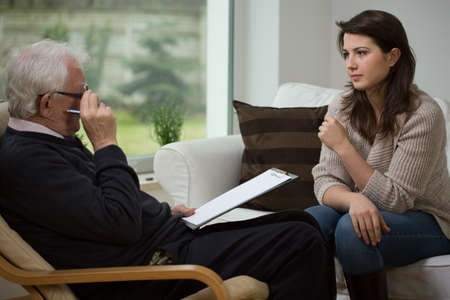 Foto de Young woman talking with her older psychologist - Imagen libre de derechos